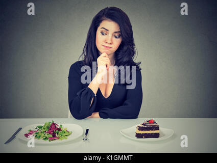 Dieting concept, beautiful young woman choosing between healthy food and tasty cake - Stock Photo