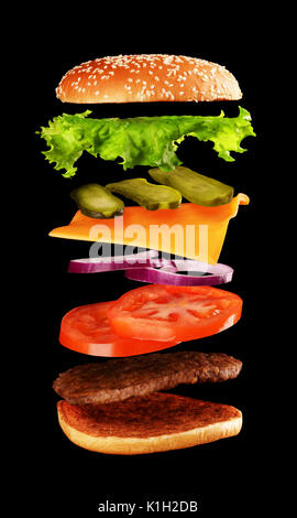 Big tasty home made burger with flying ingredients on black background. - Stock Photo