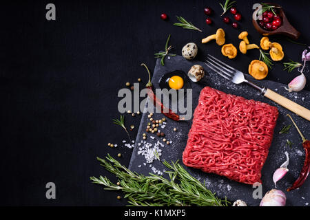 Tasty raw veal or beef meat on black table. Cooking ingredients with ground meat. Top view, copy space. - Stock Photo