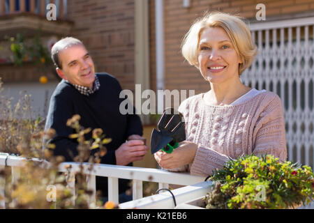 Smiling aged woman with horticultural sundry and aged man drinking tea in patio - Stock Photo