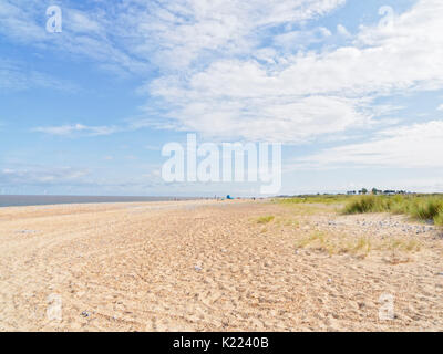 On a wide empty beach in Caister-on-Sea with a small group of people in the distance. Far out to sea are wind turbines. - Stock Photo