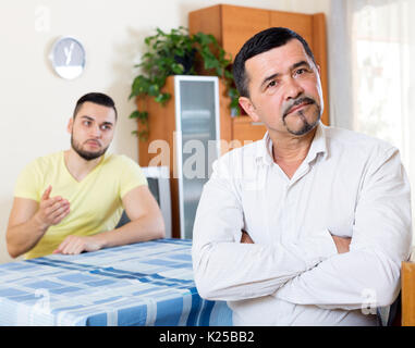 Domestic quarrel between senior father and adult son - Stock Photo