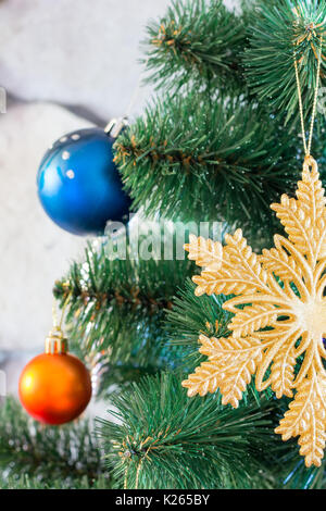 colored toys on branches of an artificial Christmas tree - Stock Photo