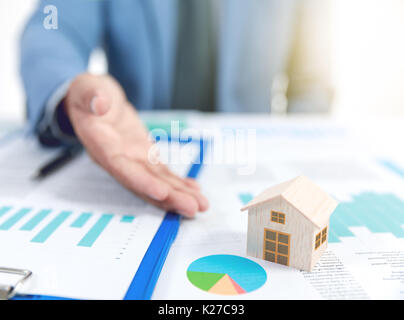 businessman show wooden home model and business graph, insurance concept - Stock Photo