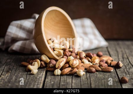 Different types of nuts. Hazelnuts, walnuts, almonds, brazil nuts and pistachio nuts on old wooden table. - Stock Photo