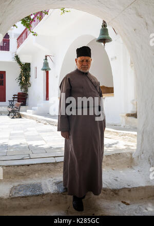 One of the Monks walking down stairs, Panagia Tourliani Monastery, Ano Mera, Mykonos, Greece. - Stock Photo