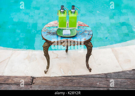 Two bottles of shampoo and handmade soap on old small vintage painted table near private luxury pool. Shower and - Stock Photo
