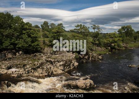 Blue sky over cascading water & limestone rocks at sunny, scenic Linton Falls waterfall over River Wharfe, Grassington, - Stock Photo
