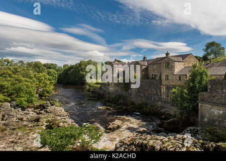 Blue sky over cascading water & riverside houses at sunny, scenic Linton Falls waterfall over River Wharfe, Grassington, - Stock Photo