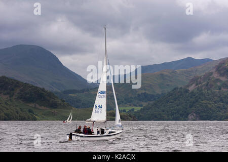 By rolling hills & under grey sky, people are sailing in small  boats on Ullswater - view to Glenridding & Patterdale, - Stock Photo