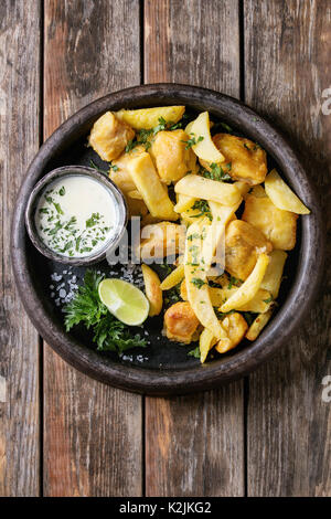 Traditional british fast food fish and chips. Served with white cheese sauce, lime, parsley, french fries in frying - Stock Photo