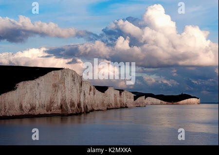 A dramatic view of the Seven Sisters at sunset. The Seven Sisters are a series of white chalk cliffs of the South - Stock Photo