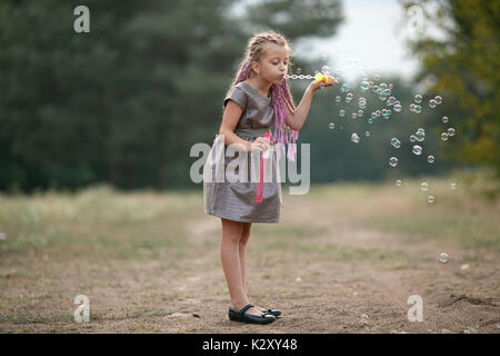 Happy child girl with pigtails blowing soap bubbles on walk in park. - Stock Photo