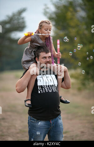 Happy father with daughter blowing soap bubbles on walk in park. Dad put child girl on his shoulders. - Stock Photo