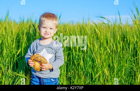 happy child in the wheat field with bread - Stock Photo