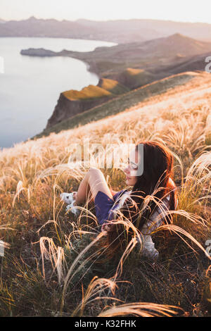 Young woman relaxing in feather grass field at sunset. Enjoying beautiful mountain view and sea coast in Koktebel - Stock Photo