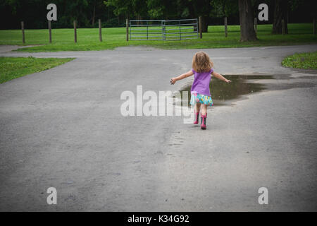 A toddler girl runs toward a mud puddle in a park. - Stock Photo
