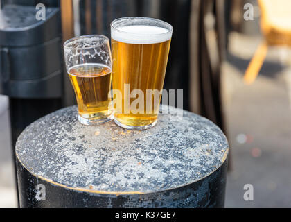 British pint and half pint of beer resting on a concrete stool, UK - Stock Photo