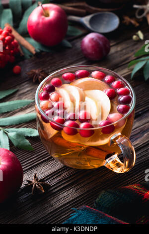 Warming winter berry tea with cranberries, apple, cinnamon, lemon, honey and thyme in a glass cup on wooden table. - Stock Photo