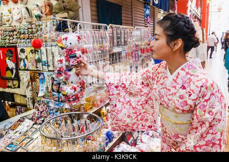 Japan, Hoshu, Tokyo, Asakusa, Nakamise Shopping Street, Girl in Kimono Buying Souvenirs - Stock Photo