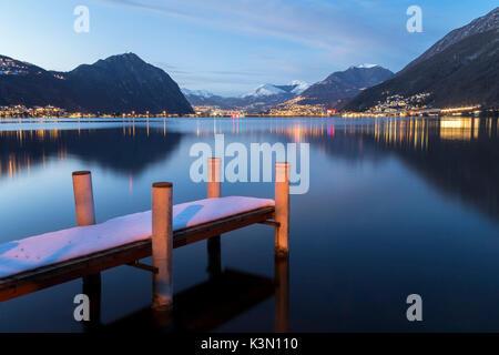 Evening lights of Lugano and Campione d'Italia in front of a pier on Lake Ceresio, Riva San Vitale, Canton Ticino, - Stock Photo