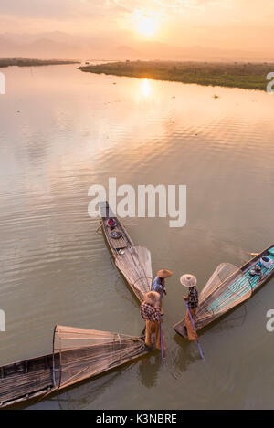Inle lake, Nyaungshwe township, Taunggyi district, Myanmar (Burma). Thee local fishermen with the conic nets on - Stock Photo