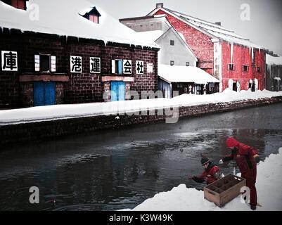 Workers placing lanterns into the Otaru Canal for the winter night illumination, Otaru, Hokkaido, Japan - Stock Photo