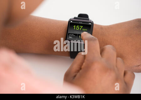 Close-up Of Hand Wearing Smartwatch Showing Heartbeat Rate - Stock Photo