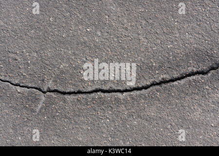 cracked asphalt with one crack - Stock Photo