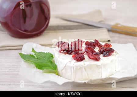 Dried cranberries on camembert cheese. - Stock Photo