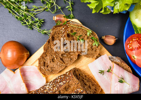 Top view of bread slices on wooden chopping board with herbs, ham and vegetables - Stock Photo