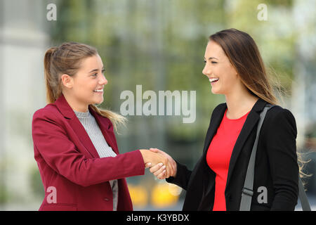 Side view of two happy executives meeting and handshaking on the street - Stock Photo