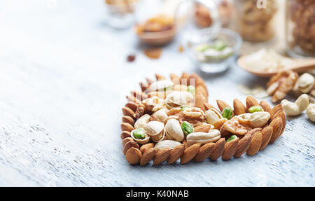 Mixed nuts forming a heart-shape on white painted wood background - Stock Photo