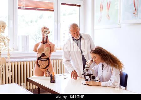 Senior teacher teaching biology to high school student in labora - Stock Photo
