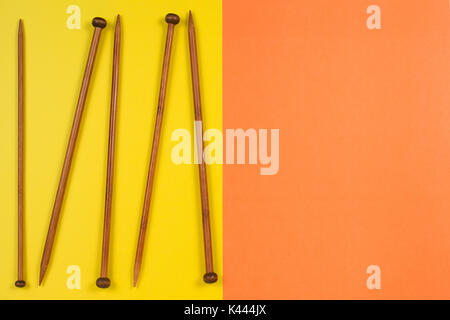 Variety of bamboo knitting needles in different sizes on yellow and orange background - Stock Photo