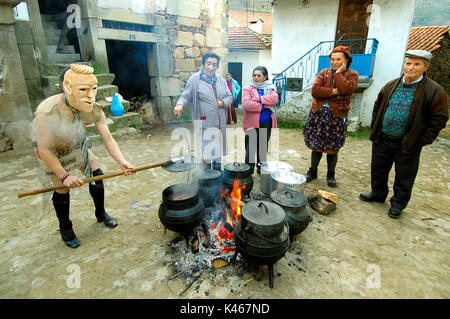 Careto cooking food for all the people during the carnival in Podence. Tras os Montes, Portugal - Stock Photo