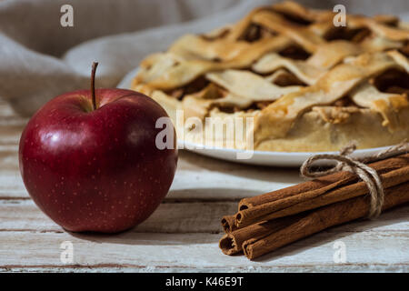 fresh apple and cinnamon sticks with homemade apple pie behind on wooden tabletop - Stock Photo