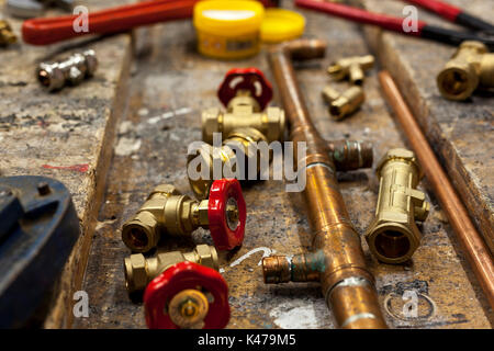 Gate valves and various plumbing fittings with copper pipe on a old wooden workbench - Stock Photo
