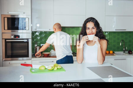 Happy young couple having coffee in the kitchen - Stock Photo