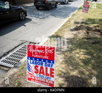 Signs placed along Queens boulevard in Queens In New York advertise the Labor Day sale of the Huffman Koos chain - Stock Photo