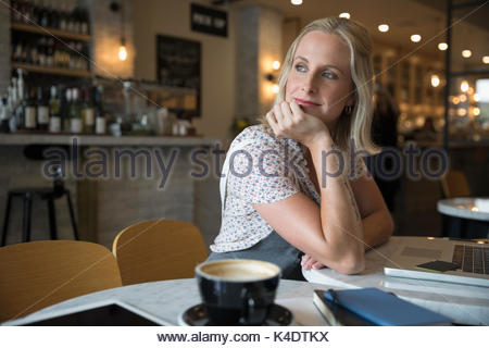 Smiling pensive woman using laptop, looking over shoulder in cafe - Stock Photo