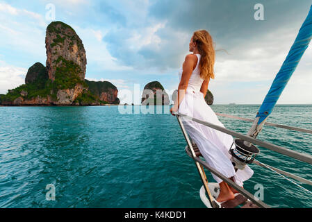 Joyful young woman portrait. Happy girl on board of sailing yacht have fun discovering islands in tropical sea on - Stock Photo