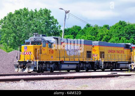 A pair of Union Pacific Yard locomotives idle near grain elevators and Waukegan Harbor in Waukegan, Illinois, USA. - Stock Photo