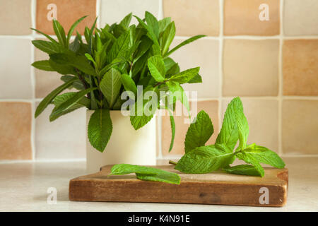 Sprigs of fresh garden mint leaves in a ceramic pot and also placed on a small wooden chopping board on a kitchen - Stock Photo