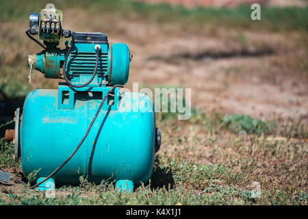 Blue water pumping station in garden - Stock Photo