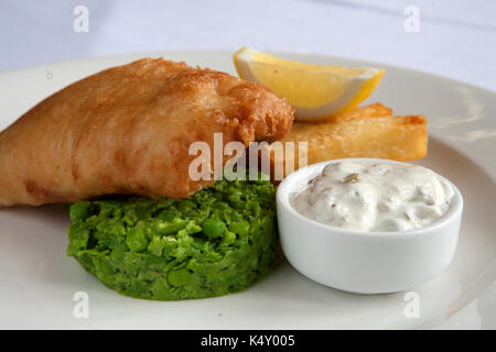 Battered fish and chips with mushy peas and tartar sauce on a plate - Stock Photo
