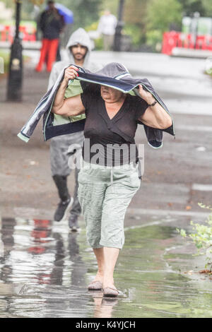 London, UK. 7th Sep, 2017. A woman shelters from the rains in Regents Park as the wet weather arrives in London - Stock Photo