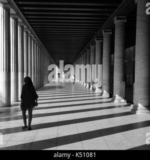 ATHENS, GREECE - OCTOBER 14, 2015: People in stoa attalos at the ancient agora. Light and shadow through marble - Stock Photo