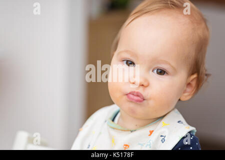 One year old baby girl feeding herself with her fingers, baby led weaning; concept of motherhood and parenting - Stock Photo