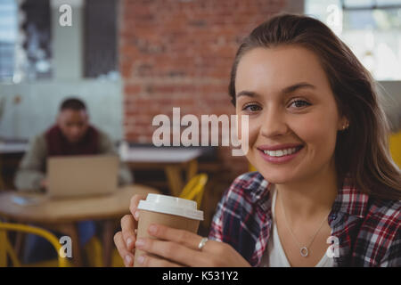 Portrait of happy young woman holding coffee cup at cafe - Stock Photo